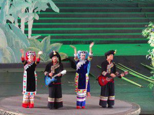 On the stage, the minority group De'ang people are playing a traditional song.